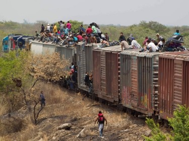 Mexican migrants migrants clamber atop a freight train bound for the U.S.-Mexican border