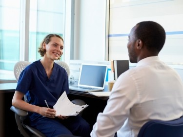 Doctor talking with her male patient in an office