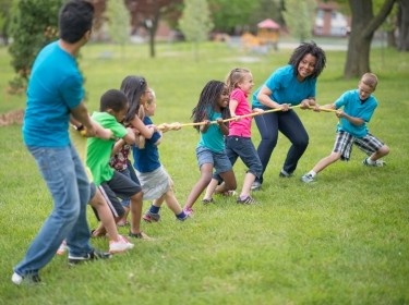 Adults and children playing tug of rope in a neighborhood park