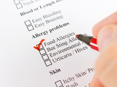 Hand with a pen checking off allergies on a medical form