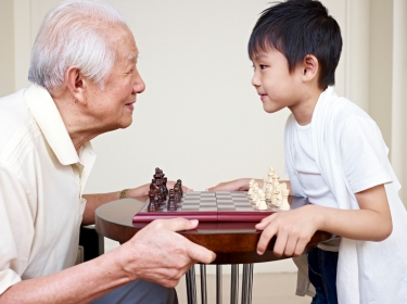 Grandpa and grandson playing a chess game
