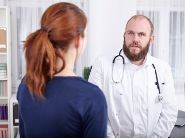 A doctor looks distracted while talking to a patient