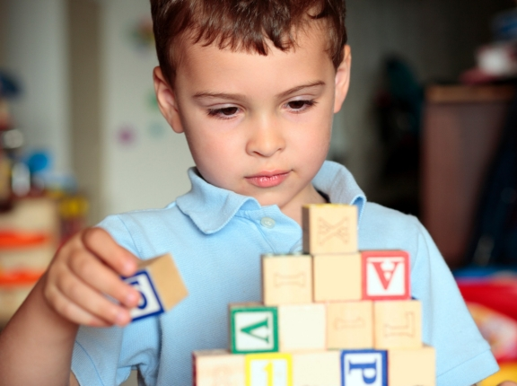 Autistic boy building with blocks, photo by Linda Epstein/iStock