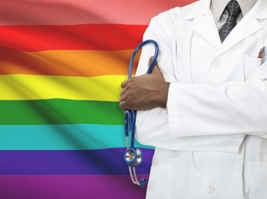 A doctor in front of a rainbow flag,