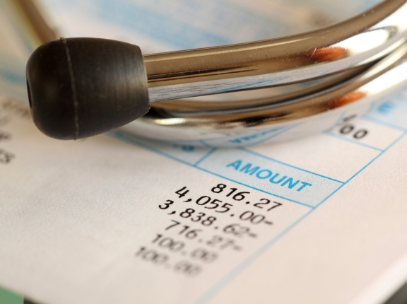 Stethoscope on top of hospital bill, photo by Kameleon007/iStock