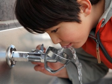Boy drinking from a water fountain