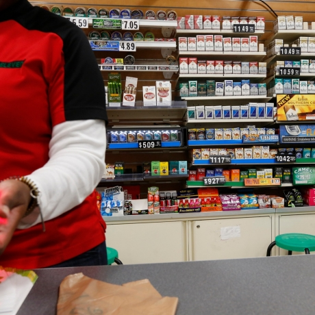 Cigarettes are displayed behind the counter of a convenient store, photo by Brendan McDermid/Reuters