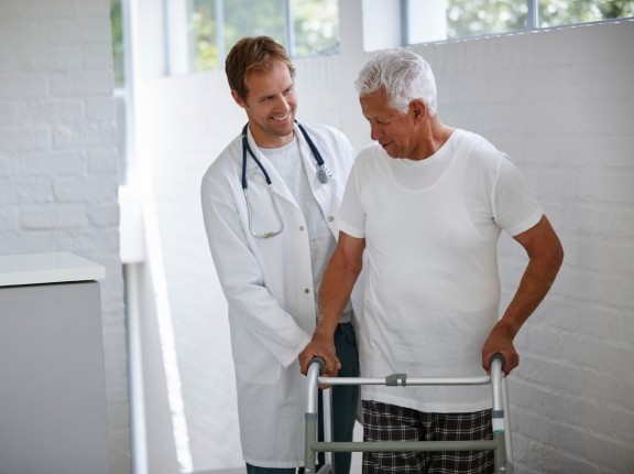 A doctor and a senior patient using a walker, photo by laflor/iStock