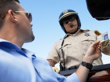 Man handing drivers license to officer