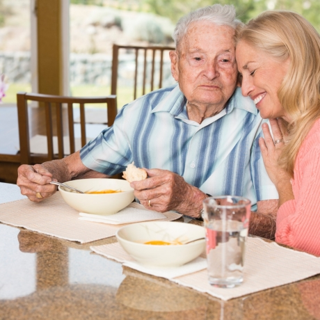 Senior man and adult daughter enjoying time together over lunch, photo by Alina555/iStock