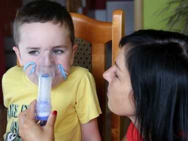 A woman helps a boy use a nebulizer