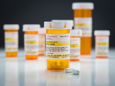 Medicine bottles and pills on a reflective surface with grey background