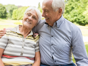 Smiling older couple sitting on a park bench
