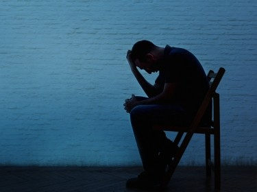 Depressed man sitting in a chair silhouetted against a brick wall