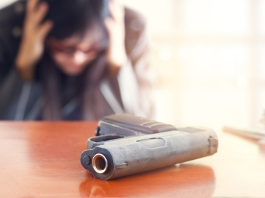 Close up of a handgun on a table, with a person in the background