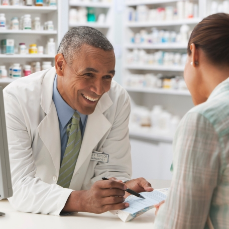 Pharmacist discussing prescription with customer, photo by SelectStock/Getty Images