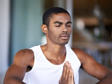 African American male meditating at home