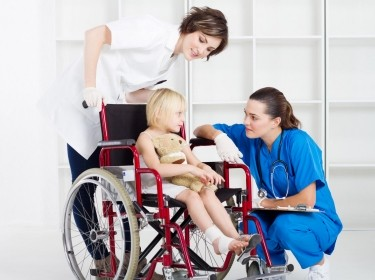 Nurse and doctor talking to a young girl in a wheelchair