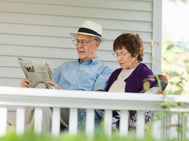 An older couple reading on a porch