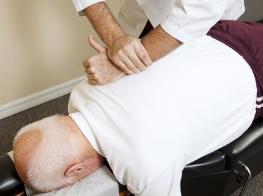 Closeup of chiropractors hands doing spinal adjustment on an older man