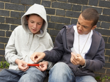 Teen boys sitting in front of a brick building, making a joint