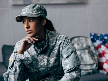 Pensive female soldier resting her chin on her hand