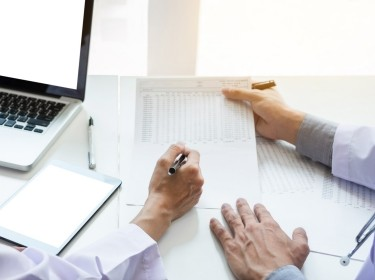 Close up of a doctor's hands holding a cost over a desk while another doctor's hand, holding a pen, points to the paper