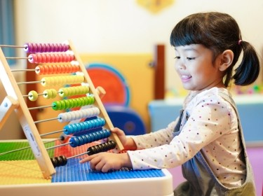 Cute Asian little kid girl playing with abacus at home. Smart child learning to count. learning, classroom, lesson concept, photo by Asada/AdobeStock