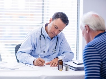 Doctor prescribing medicine to senior patient in clinic, photo by Wavebreakmedia/Getty Images