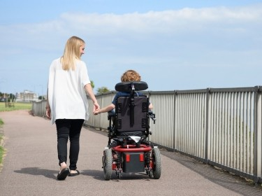 Woman walking next to, and holding hands with, her son in a wheelchair, photo by JohnnyGreig/Getty Images