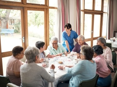 Staff person talks to a group of women dining at a nursing home, photo by shapecharge/Getty Images