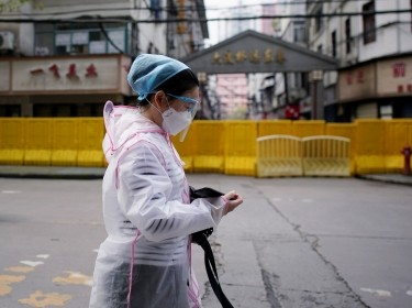 A woman wearing a face mask walks through a residential area blocked by barriers in Wuhan, Hubei province, April 3, 2020, photo by Aly Song/Reuters