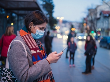 Woman waiting at a bus stop, wearing a mask and looking at a smartphone, photo by ArtistGNDphotography/Getty Images
