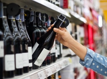 A hand reaching for a bottle of wine on a store shelf. Photo by ipopba / Getty Images