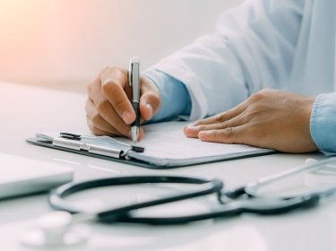 Doctor writing a prescriptions with stethoscope in foreground, photo by witsarut sakorn/Getty Images