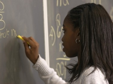 Student writing math problem on chalkboard, photo by Isaiah Love/Adobe Stock