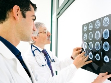 Two male doctors examine an MRI scan of the brain