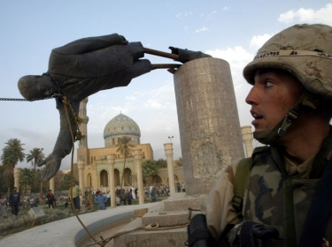 U.S. marine watches as a 20-foot high statue of Iraq's President Saddam Hussein falls in central Baghdad in April 2003