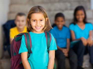 Girl with backpack with classmates at school