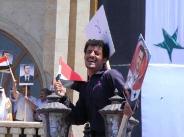A man sits atop a lamp post waving pictures of Bashar Al Assad