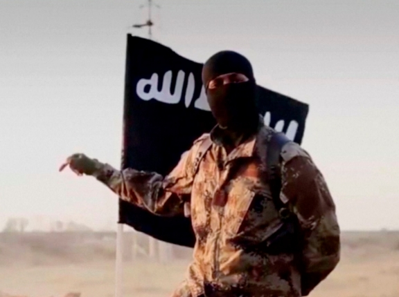 A masked man speaking in what is believed to be a North American accent in a video that Islamic State militants released in September, photo from Reuters/FBI handout