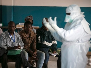 A health worker demonstrates putting on protective gear in a Red Cross facility in Koidu, Sierra Leone, December 18, 2014