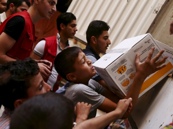 Boys help members of the Syrian Arab Red Crescent unload parcels of medical and humanitarian aid in Damascus, Syria, July 23, 2015, photo by Bassam Khabieh/Reuters