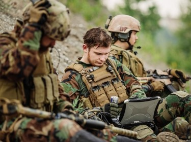 Soldiers using laptop outdoors
