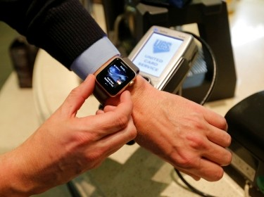 A man uses an Apple Watch to demonstrate the mobile payment service Apple Pay at a cafe in Moscow, Russia, October 3, 2016