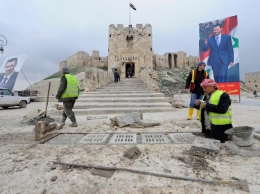 Workers repair the damage in front of Aleppo's historic citadel, as posters depicting Syria's President Bashar al-Assad are erected in the Old City of Aleppo, Syria, January 31, 2017