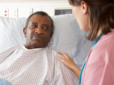 A nurse talking to a senior patient in a hospital