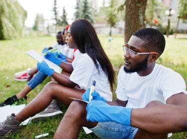Black volunteers review paperwork in a park, photo by AS photo/Adobe Stock