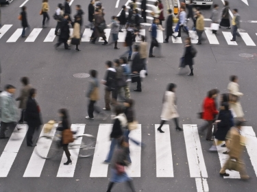 People cross a city street on their way to work