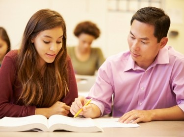 A high school student gets instruction from her teacher